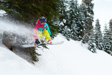 girl snowboarder jumping in the forest leaving behind spray of snow