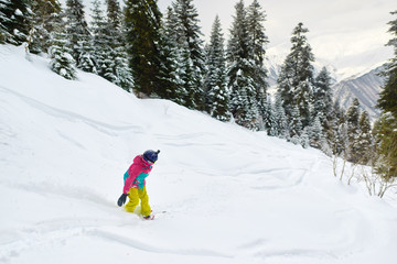 girl snowboarder rides freeride in forest