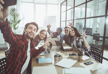 Say cheese. Overjoyed young colleagues are sitting together at table in office and taking selfie using modern mobile phone. They are smiling and positively gesturing while having pause at work