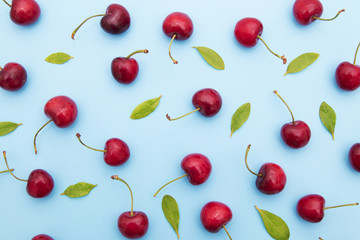 background of cherries and leaves on blue