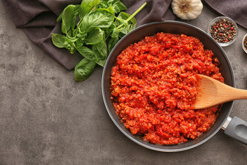 Frying pan with meat sauce on table