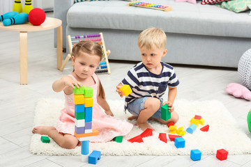 Cute children playing with constructor on floor at home