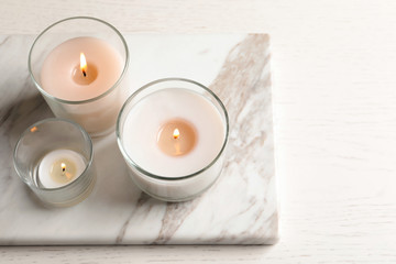 Burning candles in glasses on marble board