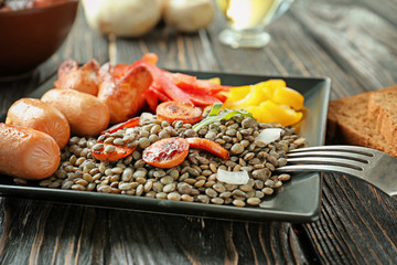 Plate with black lentils, sausages and vegetables on table
