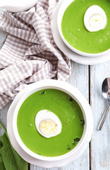 Bowls with delicious spinach soup on table