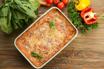 Baking dish of lasagna with spinach on wooden background