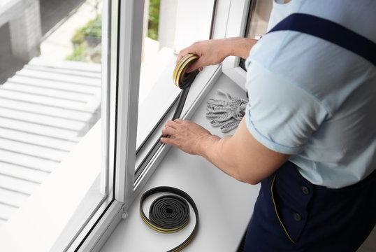 Construction worker putting sealing foam tape on window indoors