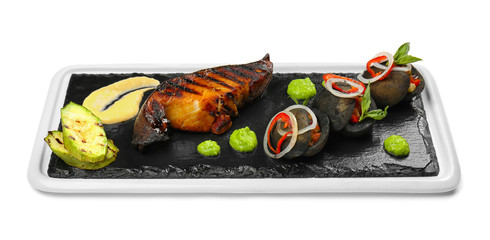 Slate plate with tasty grilled fish and garnish on white background