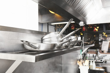Cookware on shelf in restaurant kitchen