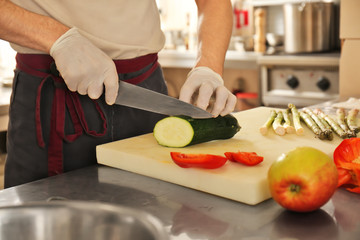 Male chef cutting vegetables in restaurant kitchen