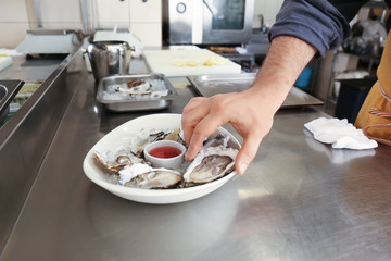 Male chef preparing fresh oysters for serving in restaurant kitchen