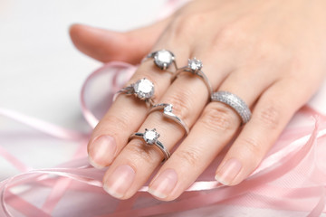 Woman wearing many different engagement rings, closeup