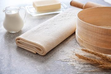 Raw flaky dough with flour on table