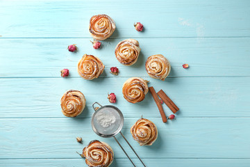 Tasty apple roses from puff pastry and sieve with sugar powder on color wooden background