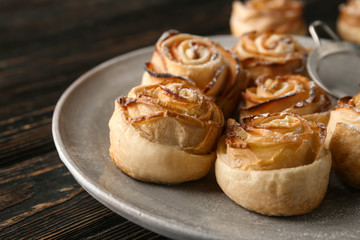 Plate with apple roses from puff pastry on table, closeup