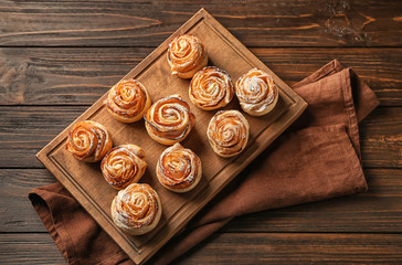 Wooden board with apple roses from puff pastry on table