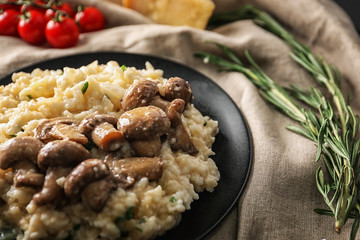 Plate with risotto and mushrooms on table, closeup