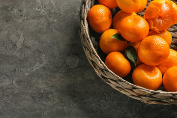 Wicker basket with juicy tangerines on table