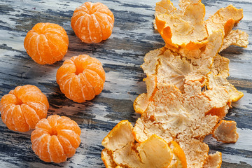 Juicy peeled tangerines and skin on wooden table