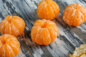 Juicy peeled tangerines on wooden table