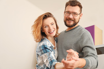 Lovely couple dancing together at home