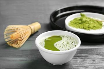 Chawan with fresh matcha tea and chasen on table