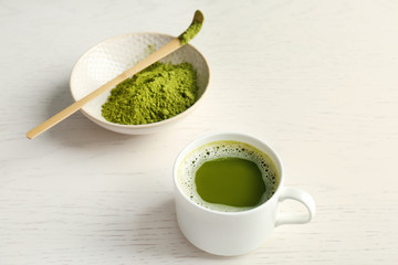 Cup of fresh beverage and chawan with powdered matcha tea on table