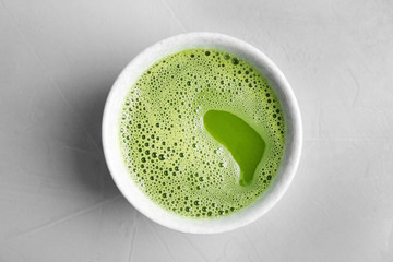 Chawan with fresh matcha tea on grey background, top view