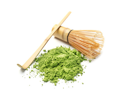Powdered matcha tea, chashaku and chasen on white background
