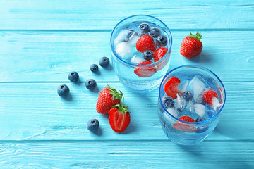 Natural lemonade with berries in glasses on wooden table