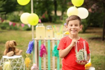 Little boy holding jar with money near lemonade stand in park