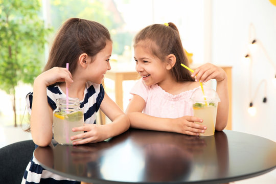 Little girls with natural lemonade at table indoors