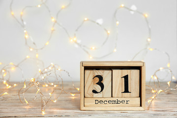 Wooden block calendar and electric garland on table. Christmas countdown