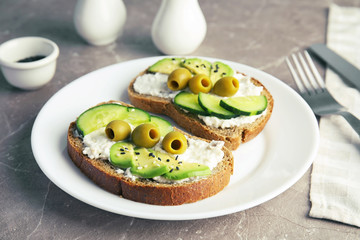 Crisp rye toasts with sliced avocado, cream cheese and olives on plate, closeup