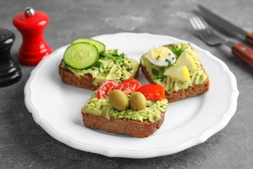 Crisp rye toasts with avocado on plate