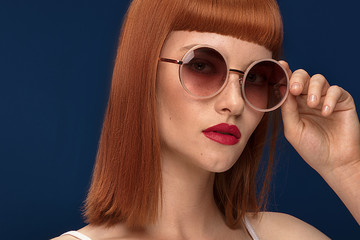 Beautiful redhead girl in sunglasses on blue background.