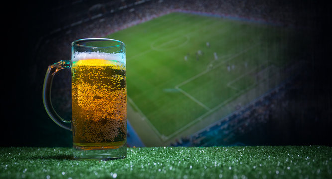 Creative concept. Pint of fresh beer on grass blurred stadium on background with fog and light. Glass of lager beer ready for drink. Copy space.