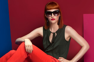 Fashionable redhead woman posing in studio.