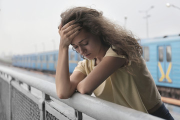 Depressed young woman at railway station