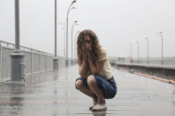 Depressed young woman on rainy day outdoors