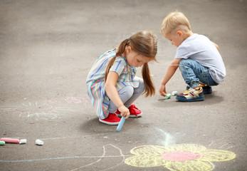 Cute little children drawing with chalk on asphalt