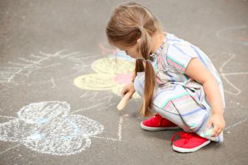 Cute little girl drawing with chalk on  asphalt