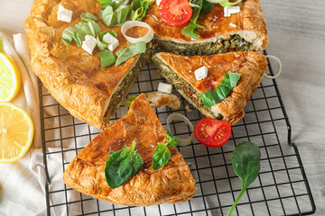 Tasty pie with spinach on cooling rack