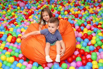 Cute children playing among plastic balls