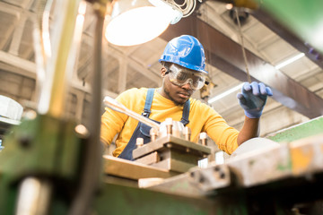 Serious busy young black factory engineer in hardhat and safety goggles examining milling lathe and repairing it while working at production plant