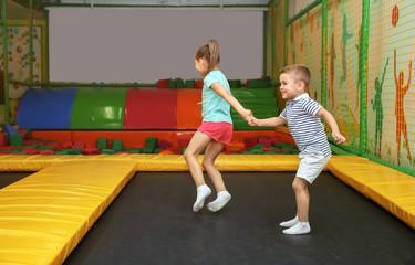 Cute children jumping on trampoline in entertainment center