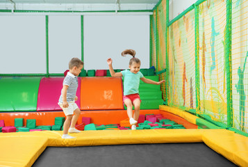 Cute children playing on trampoline in entertainment center