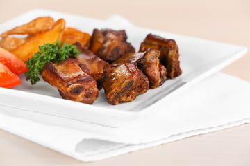 Plate with delicious grilled ribs on table, closeup