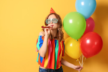 Young woman with bright balloons and party blower on color background. Birthday celebration