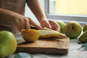 Fototapete - Woman cutting ripe pears on table